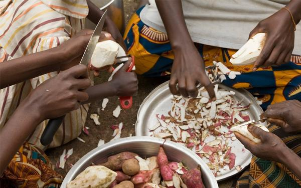 Burundi women peeling sweet potatos